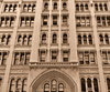 arched windows in sepia: historic city building with arched windows and old box air conditioners