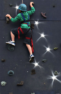 on the way up: boy climbing portable climbing wall