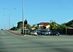 at the lights: cars at traffic lights in suburban street junction
