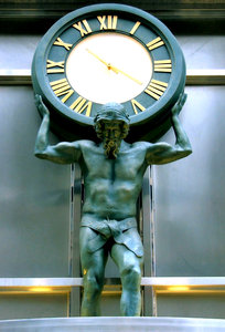the weight of time: ornamental clock and statue on historic city building