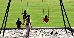 at park swings: children playing on suburban park swings