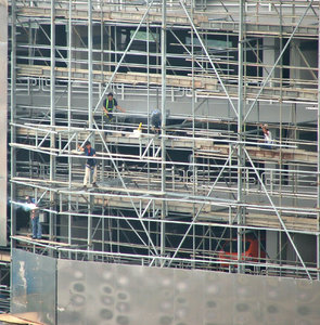 construction scaffolding: workmen high up on construction site scaffolding