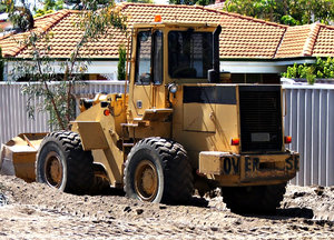 men and their machines: front-end loader clearing a suburban property