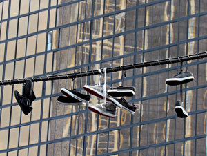 city shoes suspension: several pairs of shoes and sneakers hanging on central city street overhead powerlines