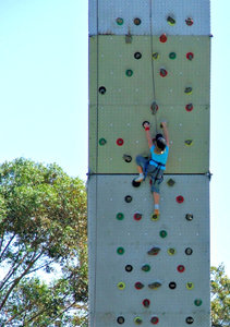on the way up: girl climbing portable climbing wall