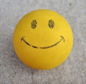 fading smile1: worn yellow smiley face rubber ball