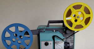 old movie time1: plastic 16mm movie reels feeding film through projector