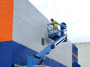 painting on high2: workman painting wall in raised cherry picker