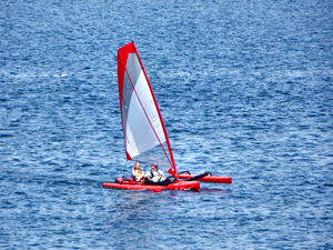 sailing on the river1: family sailing small trimaran on the river