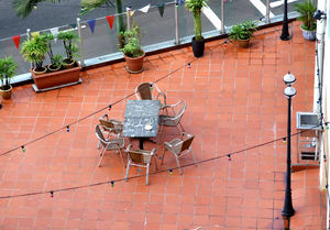 outdoor dining ambience: looking down on outdoor dining setting on balcony patio