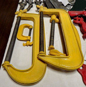 get a grip: varying sized bright yellow tradesman clamps on tool bench for holding work in place