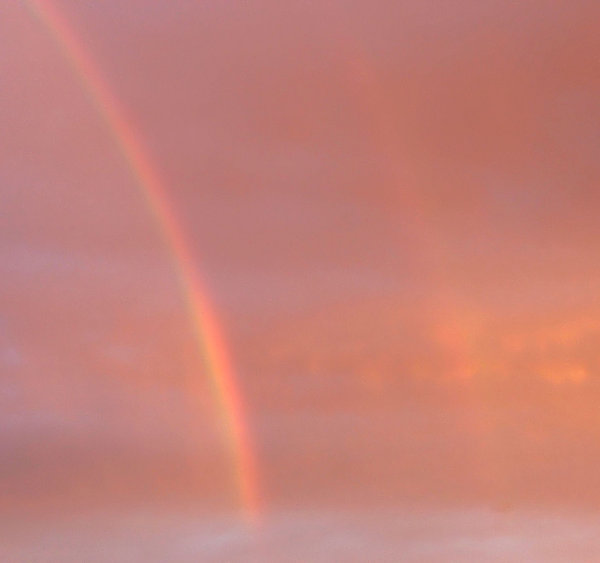 rainbow beginning: the beginning of a rainbow against a red cloudy hazy sky