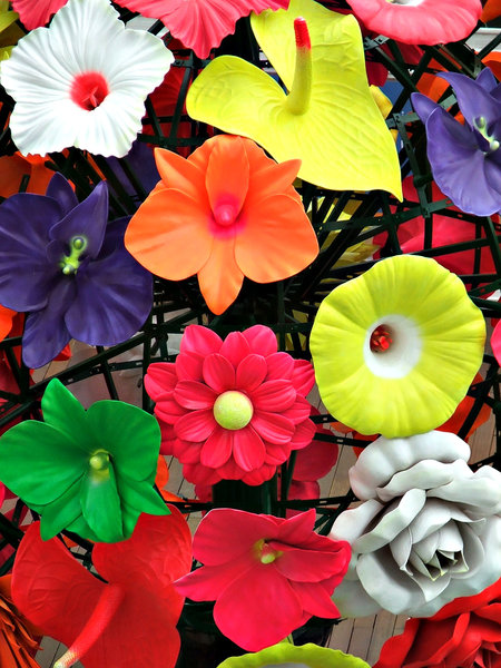 artificial colours: outdoors public display of large colourful plastic flowers