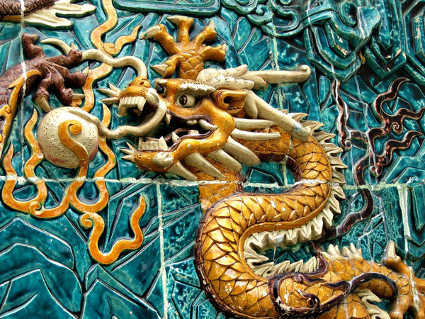 dragon closeup: close-up of dragon decorated wall alongside public footpath