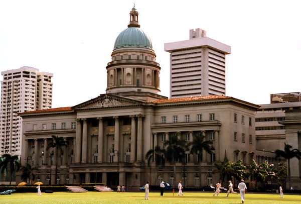 cricket before the courts: a game of cricket being played at the cricket grounds in  front of the Singapore old high court building