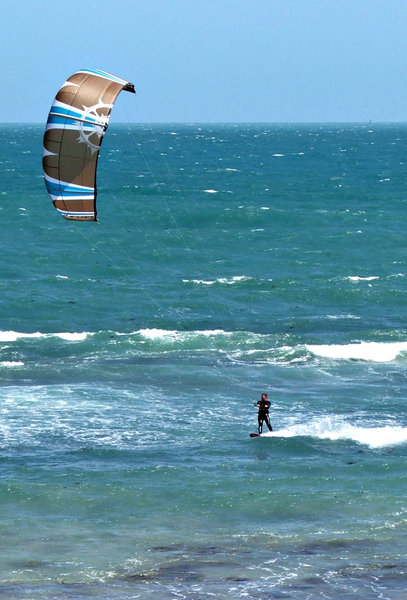 surf gliding - kite surfing: pulled along by the wind in the sails while surf gliding - kite surfing