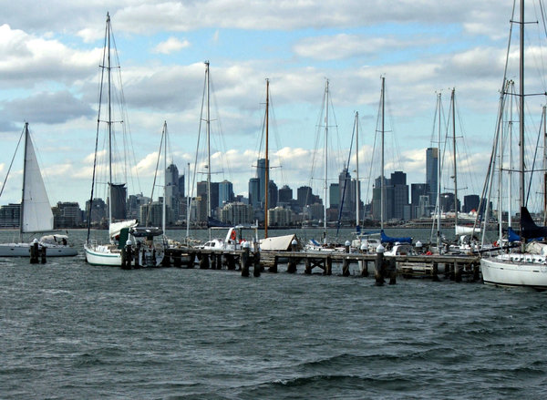 masts before the city: masts of private yachts at anchor with city skyline in the background