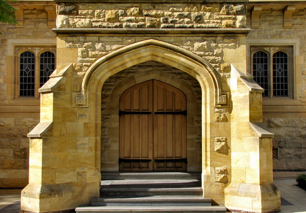 arched entrance4: closed doors on historic building's stepped arched entrance