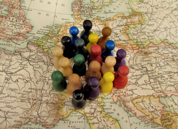 all together1b: game pieces on world map symbolizing togetherness - mixed community