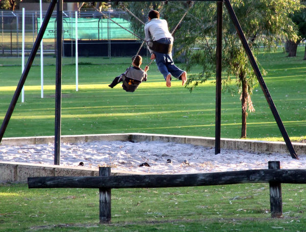 in the swing of things2: boys playing on suburban playground swings