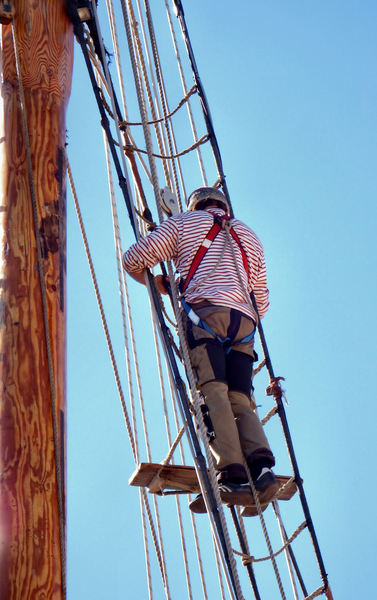up the mast11: workman - rigger doing maintenance work on tall ship's mast