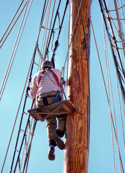 up the mast17: workman - rigger doing maintenance work on tall ship's mast