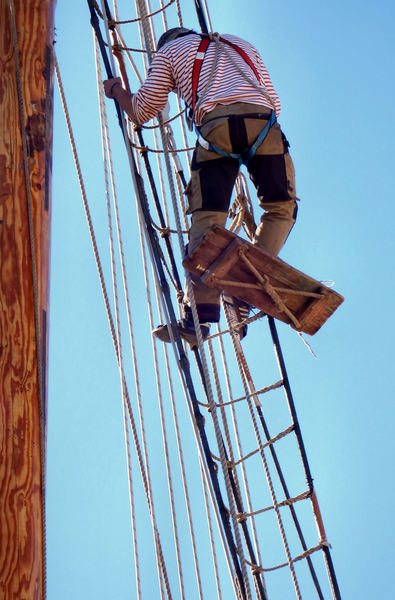 up the mast13: workman - rigger doing maintenance work on tall ship's mast