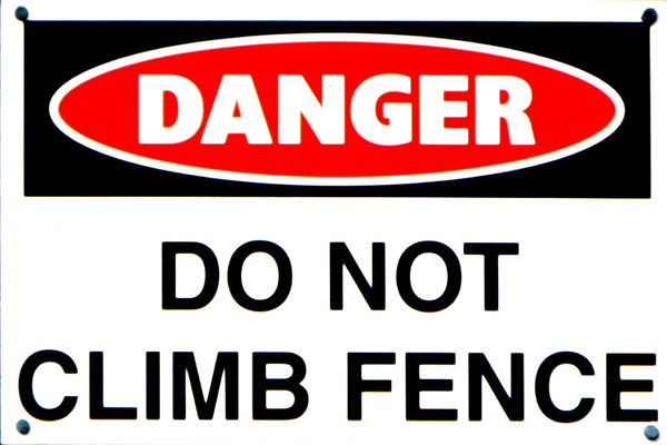 fenced in: warning sign against climbing the fence