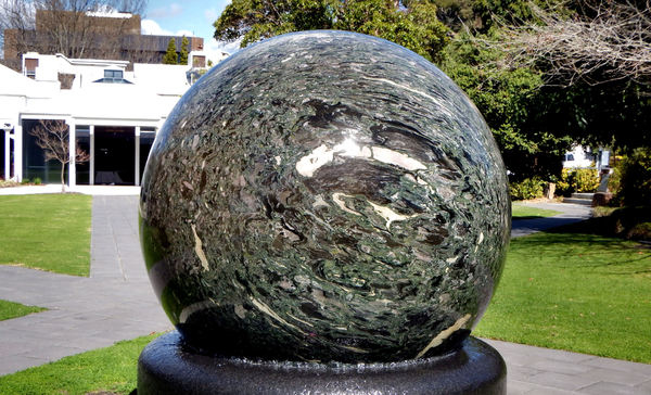 water rotating sphere2: 10 tonne kugel-ball of brecciated marble and granulitic schist floating on water on black granite base