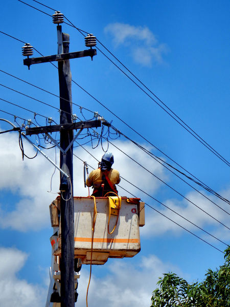 power pole replacement4: deteriorating old power pole being replaced with new pole  --  workman preparing to cut off power supply