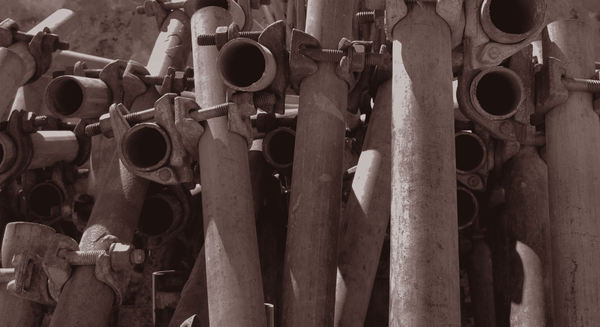 piled up pipes3: sepia image of piled up steel pipes stock