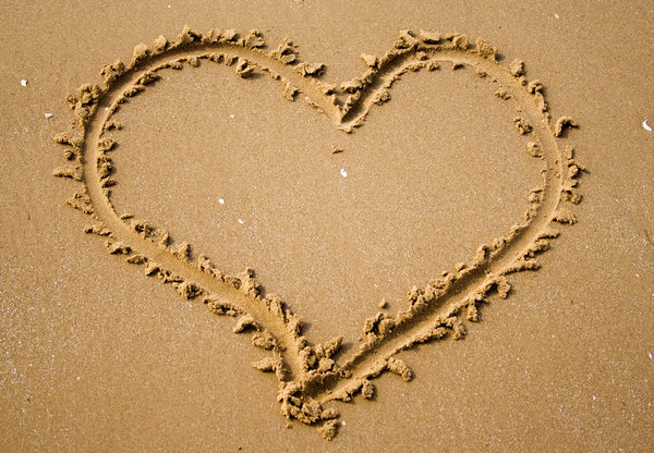 Love is a Beach: A heart drawn in the sand.  Concept of love or simply love of lazing away while on holiday.