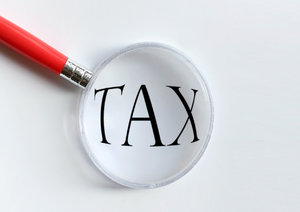 Tax: Magnifying glass over the word tax