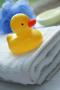 Bath Duck: Yellow plastic duck on a bath towel