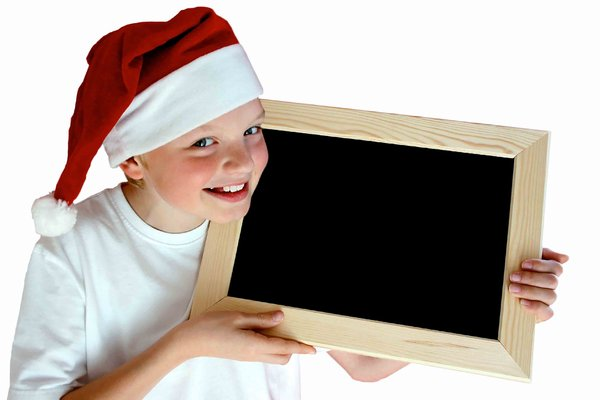 Christmas Message: Child with a Christmas hat holding a chalk board isolated over white