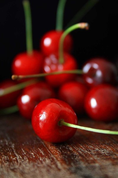 Cherries: Red sweet cherriess on a wooden surface