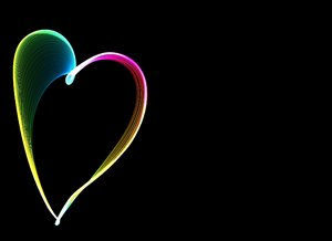 Rainbow Wave Heart: A cute, colourful heart of rainbow light on a black background. Plenty of copyspace.
