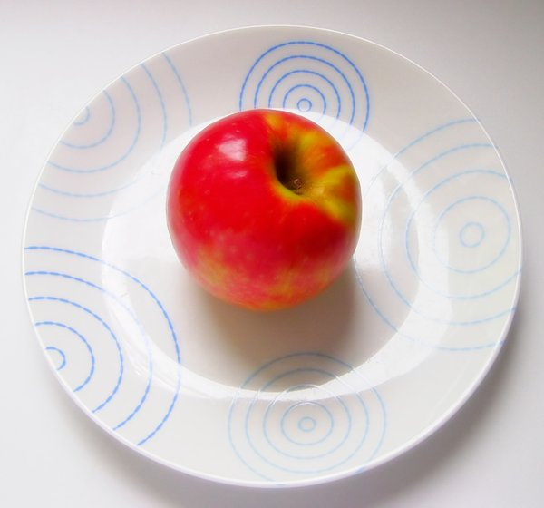 Apple on Plate: A red apple on a white plate with  blue pattern.